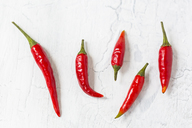 Five red chili pods on light ground - JUNF01252