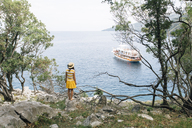 Croatia, Cres, woman standing at the coast looking at the sea with sailing ship - JES00153
