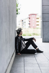 Punk woman sitting at a wall - GIOF04422