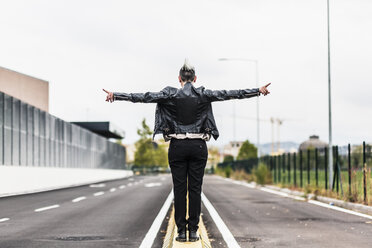 Rear view of punk woman standing on a barrier at the roadside with outstretched arms - GIOF04425