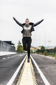 Punk woman jumping on a barrier at the roadside - GIOF04428