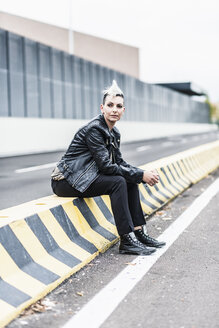 Punk woman sitting at the roadside looking around - GIOF04431
