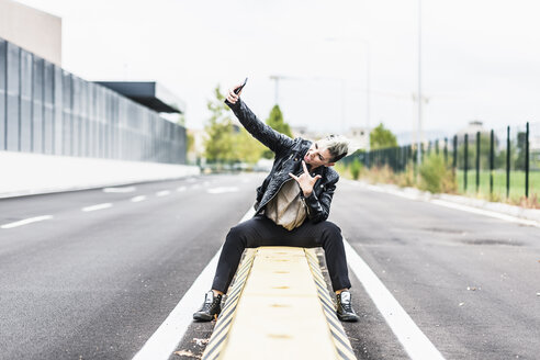 Punk woman sitting at the roadside posing for a selfie - GIOF04434