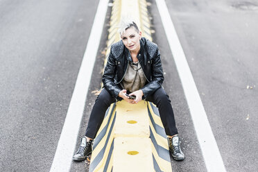 Portrait of punk woman sitting at the roadside holding cell phone - GIOF04437