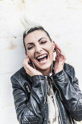 Exuberant punk woman listening to music with earbuds - GIOF04440