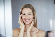 Portrait of smiling blond woman touching her face - PNEF00910
