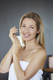 Portrait of smiling blond woman applying face cream in the morning - PNEF00913