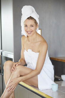 Portrait of smiling woman wrapped in towels sitting on sink in the kitchen - PNEF00916