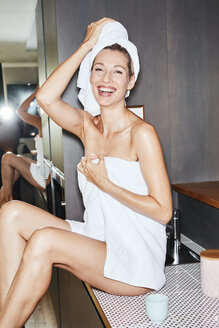 Portrait of laughing woman wrapped in towels sitting on sink in the kitchen - PNEF00919
