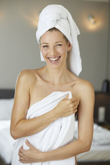 Portrait of laughing woman wrapped in towel standing in bedroom in the morning - PNEF00922