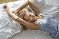 Laughing blond woman lying in bed in the morning - PNEF00925