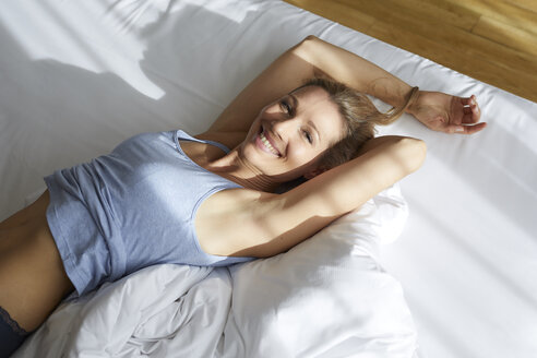 Portrait of smiling blond woman stretching in bed in the morning - PNEF00928
