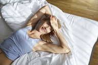Portrait of smiling blond woman lying in bed in the morning - PNEF00931