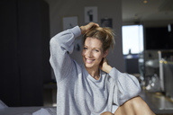 Portrait of smiling woman sitting on bed in the morning - PNEF00934