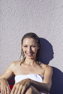 Portrait of laughing blond woman with wet hair wrapped in towel enjoying sunbath - PNEF00943