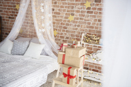 Cozy bedroom with Christmas lights and presents - ABIF01023
