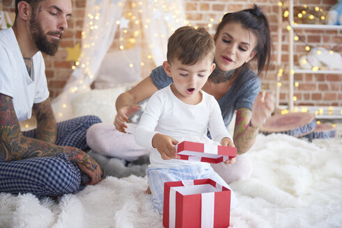 Surprised boy opening Christmas present with his parents in bed - ABIF01041