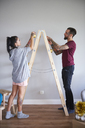 Modern couple decorating the home at Christmas time using ladder as Christmas tree - ABIF01053
