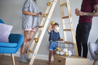 Modern family decorating the home at Christmas time using ladder as Christmas tree - ABIF01056