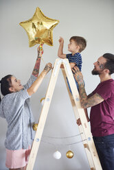 Modern family decorating the home at Christmas time using ladder as Christmas tree - ABIF01059
