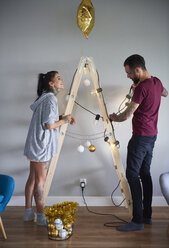 Modern couple decorating the home at Christmas time using ladder as Christmas tree - ABIF01065