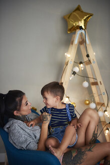 Happy boy with his mother at home at Christmas time - ABIF01068