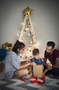 Boy opening Christmas present with his parents at home - ABIF01071