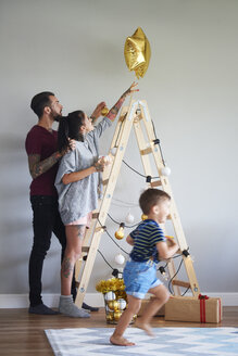 Modern family decorating the home at Christmas time using ladder as Christmas tree - ABIF01077