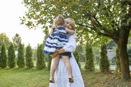 Happy mother carrying her daughter in garden - ZEDF01550