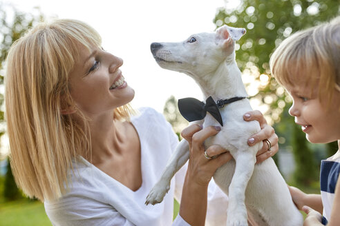 Happy woman with daughter holding dog wearing a bowtie outdoors - ZEDF01556
