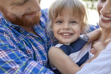 Happy parents hugging her daughter outdoors - ZEDF01565