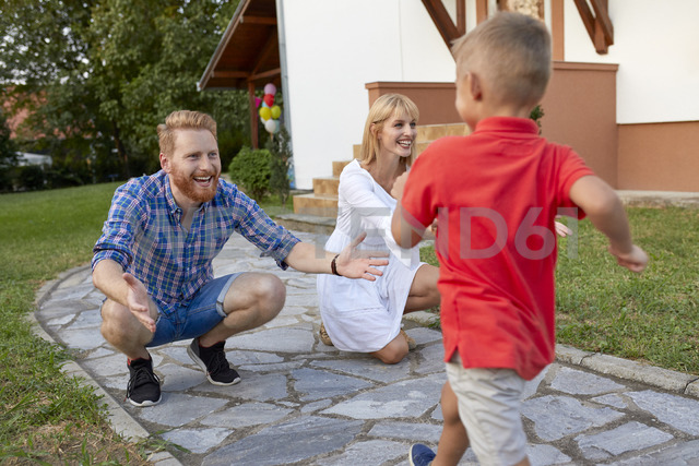 Boy running towards happy parents on garden path - ZEDF01574