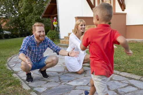 Boy running towards happy parents on garden path - ZEDF01574