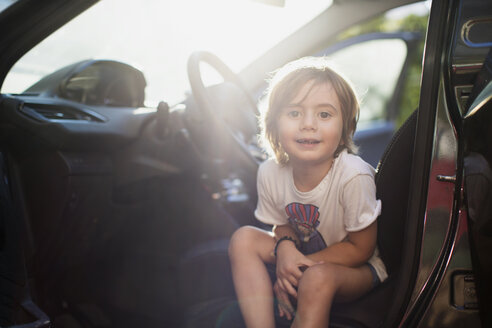 Portrait of little boy sitting on driver's seat in a car at backlight - AZOF00053