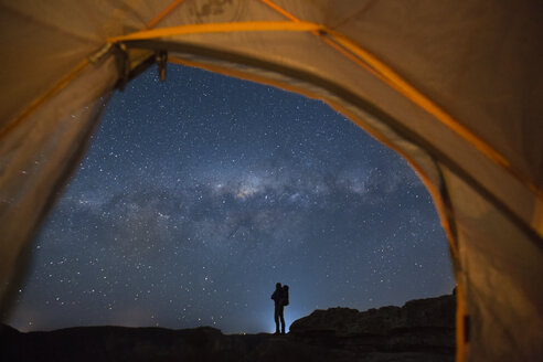 Silhouette of backpacker standing against starry night sky, New South Wales, Australia - AURF05555