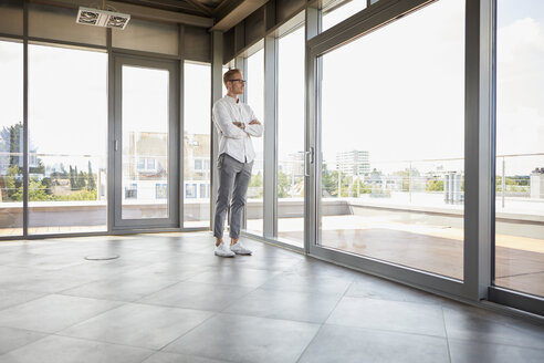Businessman standing in empty room looking out of panorama window - RBF06720
