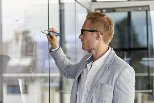 Businessman writing on glass pane in office - RBF06726