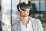 Smiling businessman wearing VR glasses - RBF06729