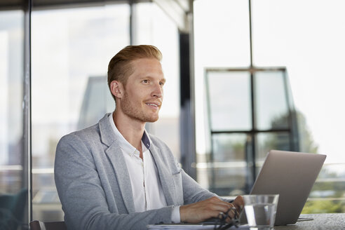 Smiling businessman with laptop on desk in office - RBF06735