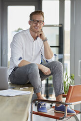 Portrait of smiling businessman with laptop sitting on desk in office - RBF06747