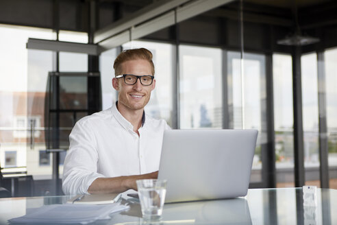 Portrait of smiling businessman using laptop on desk in office - RBF06753