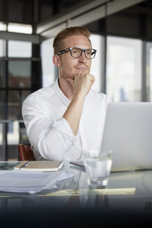 Businessman with laptop on desk in office thinking - RBF06756
