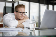 Businessman leaning on desk in office with laptop - RBF06759