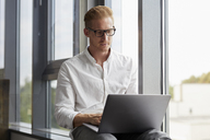 Businessman sitting on windowsill using laptop - RBF06768