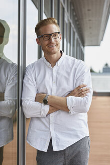 Portrait of smiling businessman leaning against window - RBF06783