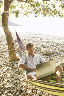 Croatia, Cres Island, man lying in hammock on a beach using laptop - JESF00159