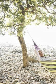 Man relaxing in hammock on the beach - JESF00165