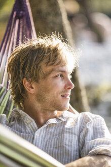 Portrait of man relaxing in hammock on a beach - JESF00168