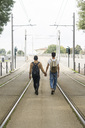 Back view of young gay couple with backpacks walking hand in hand between tracks on the road - FBAF00048