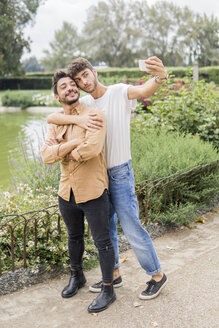 Portrait of young gay couple taking selfie with smartphone at city park - FBAF00057
